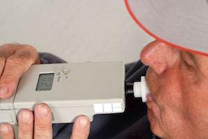 Man undergoing an alcohol test using a breathalyzer.