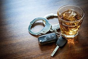 An alcoholic beverage in a glass, handcuffs, and car keys on a table top.