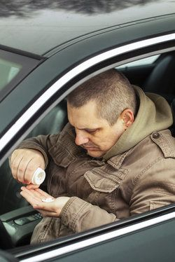 A man with pills in a car