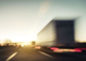 Blurred image of a large truck on the road.